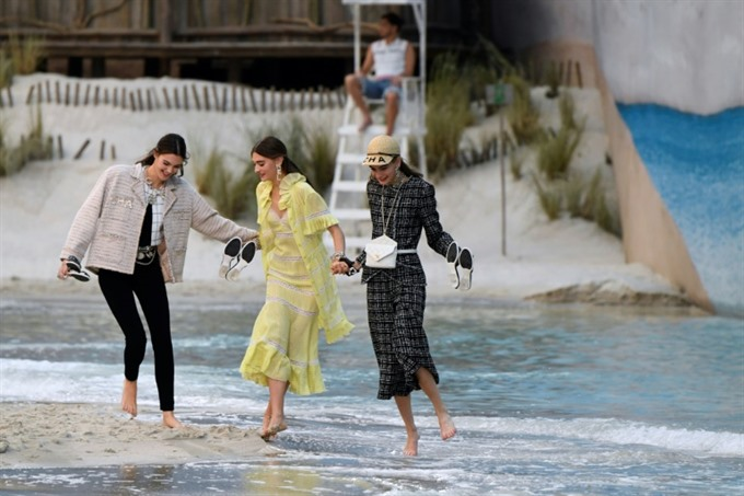 Lagerfeld takes Chanel to beach as Vuitton boosts colour