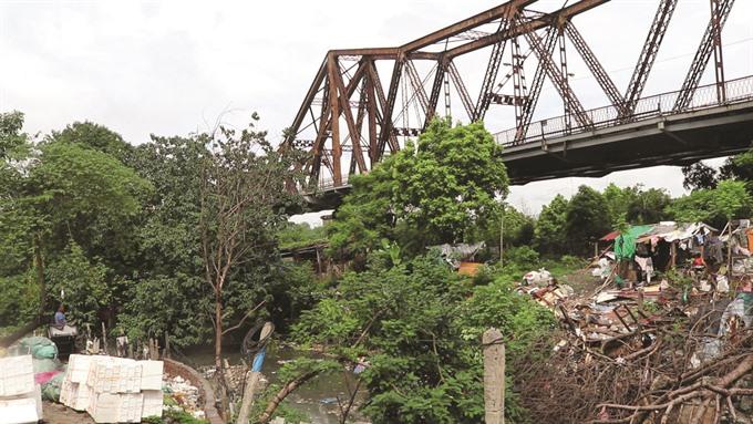 Life goes on underneath Long Biên bridge
