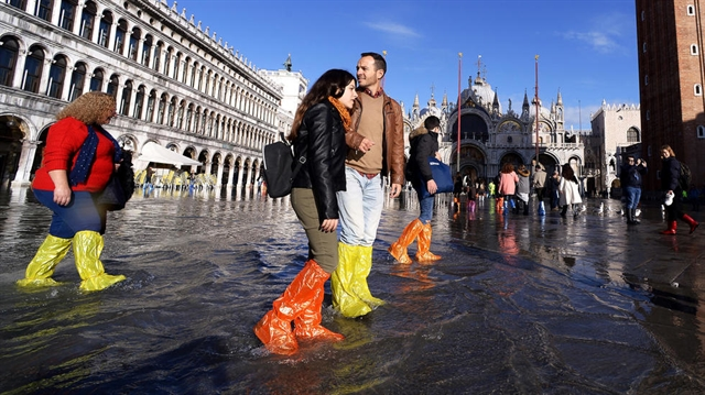 As tides rise flooded Venice awash with colourful plastic boots