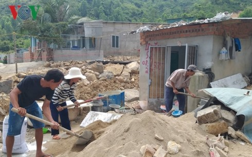 People rebuild houses after landslide despite warnings