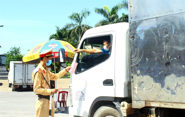 Police at Nghệ Ans COVID checkpoints work around the clock in scorching heat