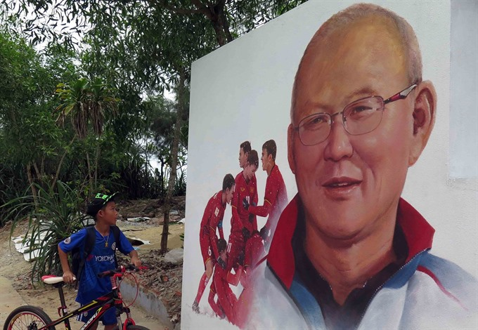 A boy looks at a portrait of Korean coach Park Hang-seo and members of the Vietnamese national football team painted on the wall of a house in Tam Thanh Commune in the central coastal province of Quảng Nams Tam Kỳ City. — VNA/VNS Photo Đỗ Trưởng