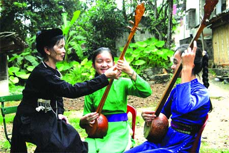 Striking a chord: Schoolgirls at Dinh Hoa High School learn how to play the tinh guitar and sing then folk songs thanks to the careful tutelage of artisan Hoang Thi Bich Hong.
