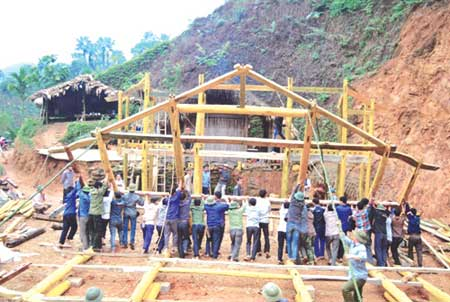 Rebuilding: Carpenters and local Muong people restore an ancient stilt house.