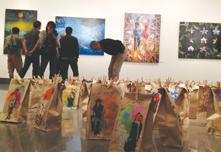 A good cause: Visitors examine paintings and installations at the on-going Sau Con Bao, or After the Storm, exhibition that pays tribute to the victims of deadly Haiyan typhoon in the Philippines.