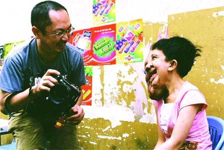 All smiles: Photojournalist Murayama Yasufumi chats with Do Thuy Duong, an Agent Orange victim, in HCM City in 2006.