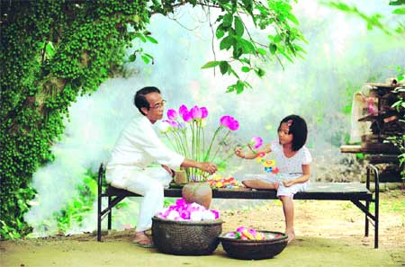 Picture perfect: A little girl lends a hand as artist Than Van Huy arranges a vase of paper lotus flowers in the backyard of his house.
