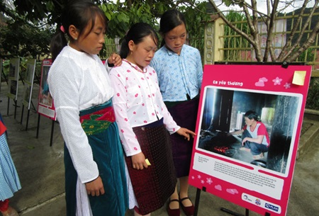 Vu Thi Vu (centre) shows her friends one of her photos on display at Can Chu Phin secondary school in Meo Vac District, Ha Giang Province.