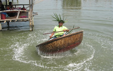 Do a little dance: A tour guide dances in a coracle. Visitors can watch funny dances performed on basket boats and play folk games during the Hoi An Eco-discovery tour.