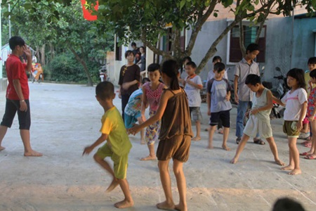 At Thuy's Hoa Sen centre, kids play a folk game after school in an April afternoon as their dinner is prepared.