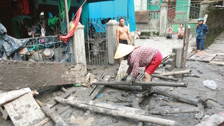Residents clean up in Mong Duong Ward, Cam Pha City, in northern Quang Ninh Province. Heavy rains, floods and tonnes of mine sludge claimed 17 lives and caused millions of dollars worth of damage in the coal mining province.