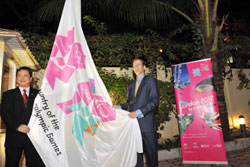 Ambassador hoists Games flag